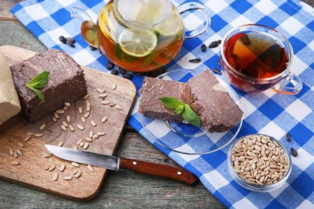 Tasty halva with cup of tea and teapot on blue napkin Stock Photo
