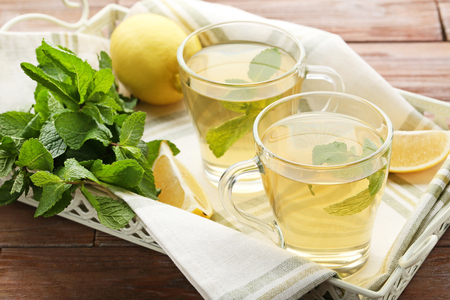 Cup of tea with mint leafs and lemons in tray