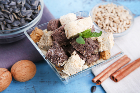 Tasty slices of halva in bowl on wooden table Stock Photo