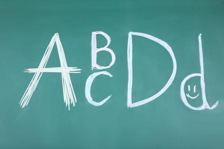 Handwritten letters ABCD on blackboard