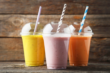 Sweet smoothie in plastic cups on wooden table Stock Photo