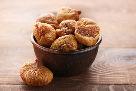 Dried figs in bowl on brown wooden table Banco de Imagens