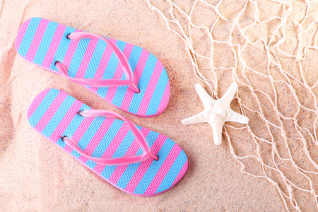 Flip flops with starfish on the beach sand Stock Photo