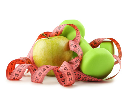 Measuring tape with green apples and dumbbells isolated on white Stock Photo