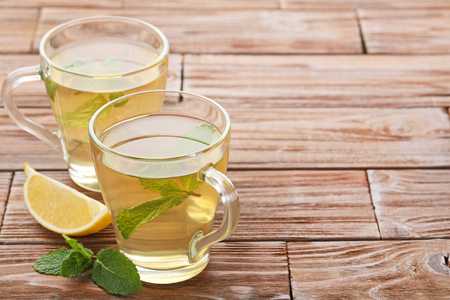 Cup of tea with mint leafs and lemon on wooden table