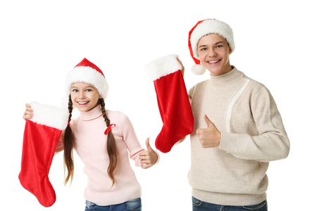 Young girl and boy in santa hats holding christmas socks on white background