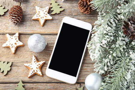 Smartphone with gingerbread cookies and fir-tree branches on wooden table