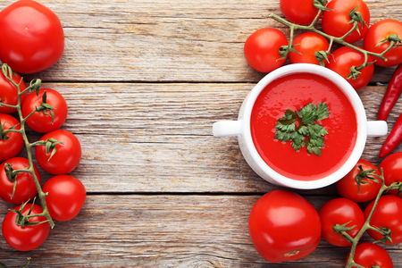 Tomato soup with parsley on grey wooden table