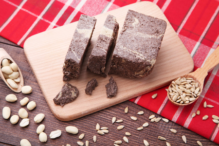 Tasty pieces of halva with cocoa on cutting board