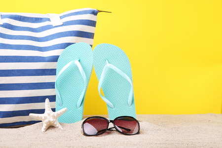 Pair of flip flops with sunglasses and starfish on the beach sand Stock Photo