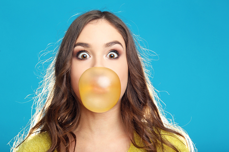 Beautiful young girl blowing bubble with chewing gum on blue background
