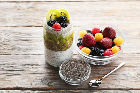 Chia pudding with berries in bottle on grey wooden table