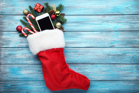 Red stocking with fir-tree branches and smartphone on wooden table