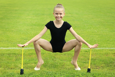 Young girl gymnast with mace on green grass