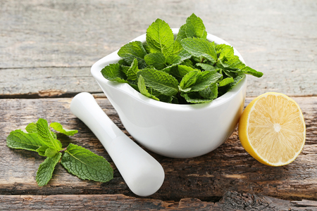Fresh mint leafs in mortar with lemon on grey wooden table Zdjęcie Seryjne