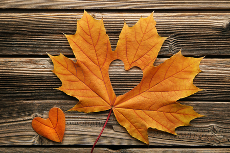 Dry maple leaf with heart on brown wooden table