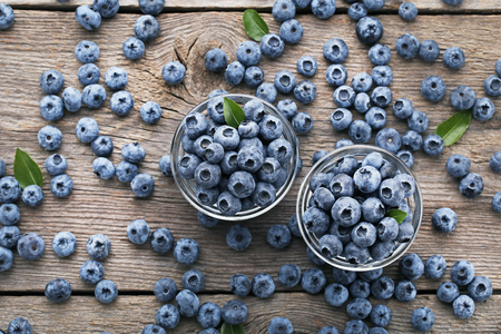 Ripe blueberries in glass bowls on wooden table