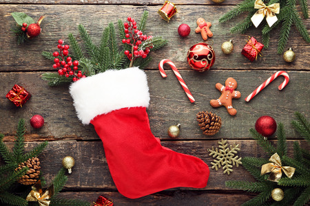 Red stocking with fir-tree branches and christmas decorations on wooden table Archivio Fotografico