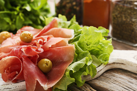 Slices of jamon with olives and lettuce on white cutting board