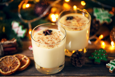 Eggnog in glasses with star anise on wooden table