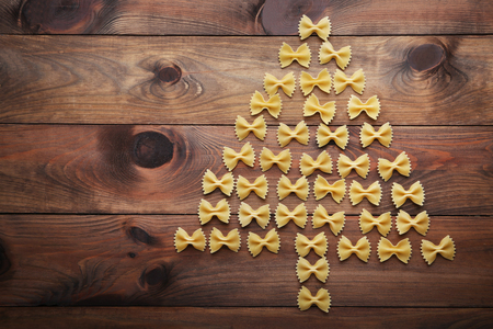 Christmas tree made from bow tie pasta on wooden table