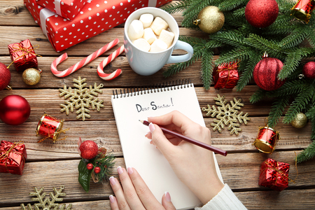Female hand writing letter to santa claus on sheet of paper Stock Photo