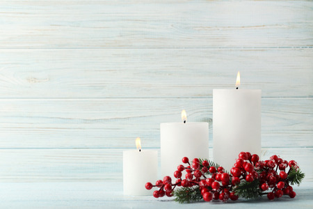 Christmas candles with red berries on wooden table Stock Photo