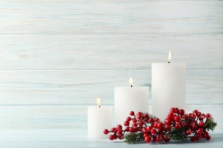 Velas de Navidad con frutos rojos sobre mesa de madera