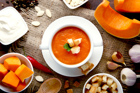Pumpkin soup with rusks and parsley in plate on wooden table
