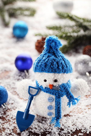 Small snowman toy with shovel on wooden table