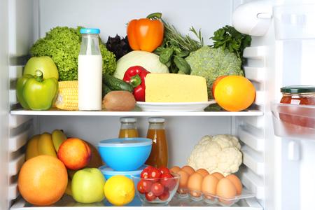 Nevera abierta llena de verduras y frutas.