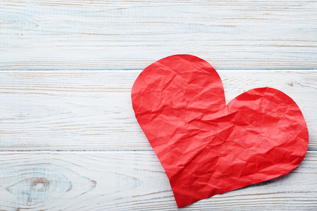 Crumpled paper heart on white wooden table