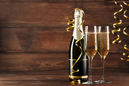 Champagne bottle with glasses on wooden table Stockfoto