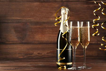 Sektflasche mit Brille auf Holztisch Standard-Bild - 91891778