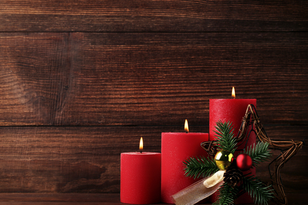 Christmas candles with fir-tree branches and baubles on wooden table