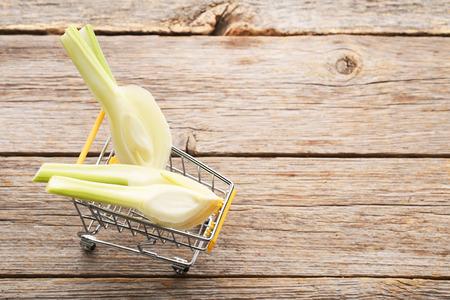 Ripe fennel bulbs in shopping trolley on grey wooden table