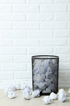 Office trashcan with crumpled paper balls