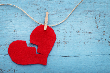 Broken red heart hanging on rope on blue wooden table Archivio Fotografico