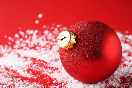 Red christmas bauble on white snow
