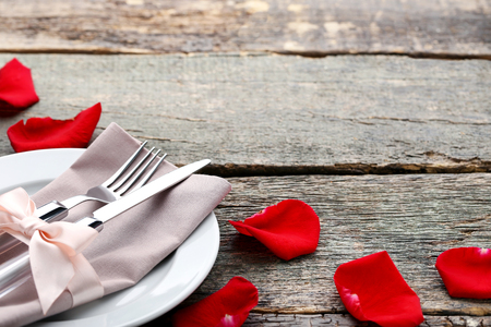 Kitchen cutlery with napkin and red rose petals on wooden table