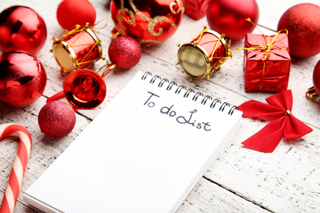 stock photo to do list in notepad with christmas decorations on wooden table - Christmas Decorations List