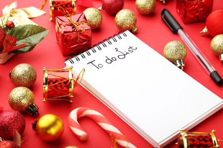 stock photo to do list in notepad with christmas decorations on red background