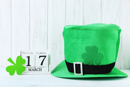 Green paper clover leafs with calendar and hat on white wooden table. St. Patricks day Stock Photo