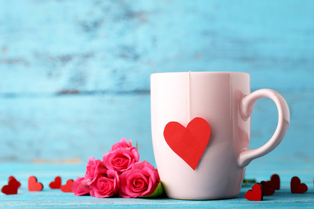 Cup of tea with red hearts and roses on wooden table
