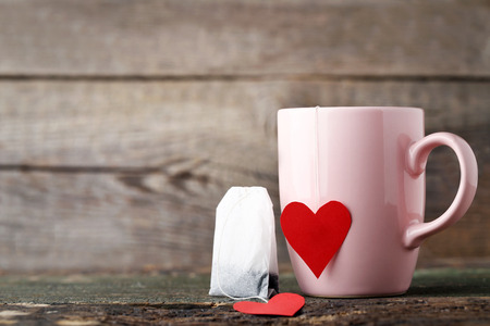 Cup of tea with red heart and teabag on wooden table Stock Photo
