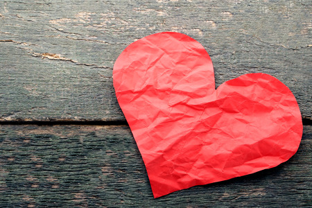 Crumpled paper heart on wooden table