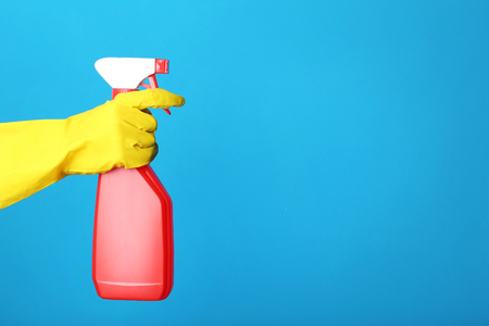 Female hand holding spray with detergent on blue background Stock Photo