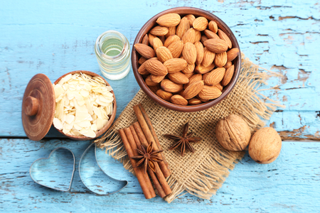 Almonds in bowl with bottle of oil on blue wooden table