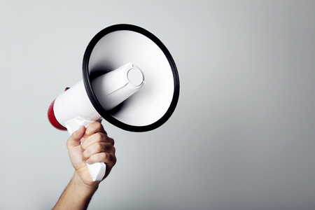 Female hand holding megaphone on grey background