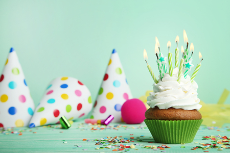 Cupcake with candles, blowers and paper caps on green background Stock Photo